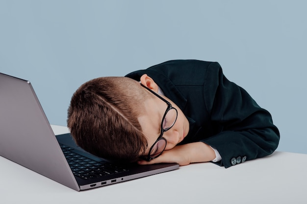 Exhausted schoolboy napping on table near laptop in studio on blue background