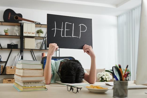 机に座ってヘルプサインを見せて勉強するのにうんざりしている疲れた男子生徒