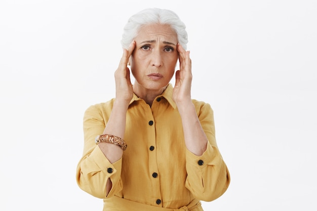 Exhausted senior woman touch head, complaining on migraine, have headache