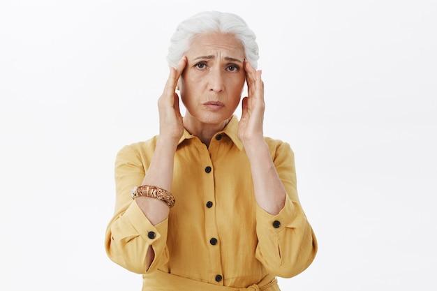 片頭痛を訴える、疲れ果てた年配の女性が頭に触れる、頭痛がある