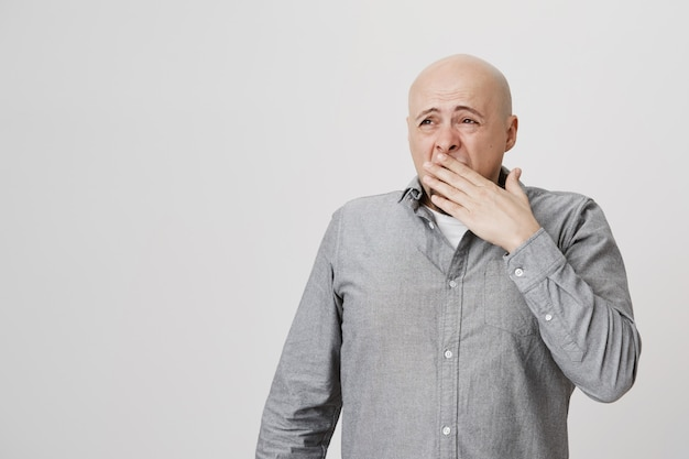 Exhausted sleepy bald adult man yawning, cover face and look left
