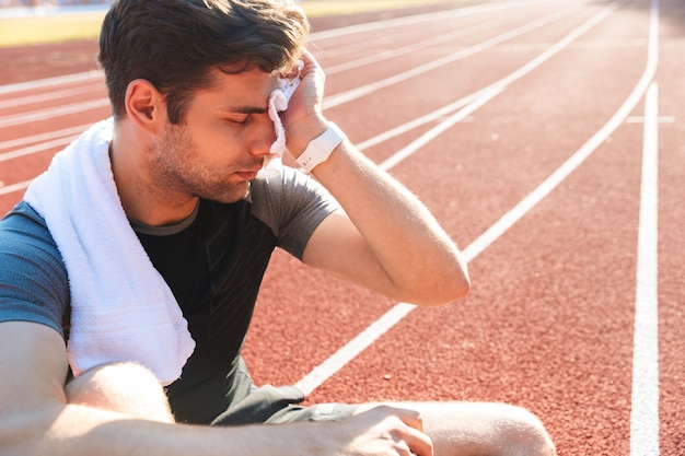 Exhausted sportsman finished running at the stadium