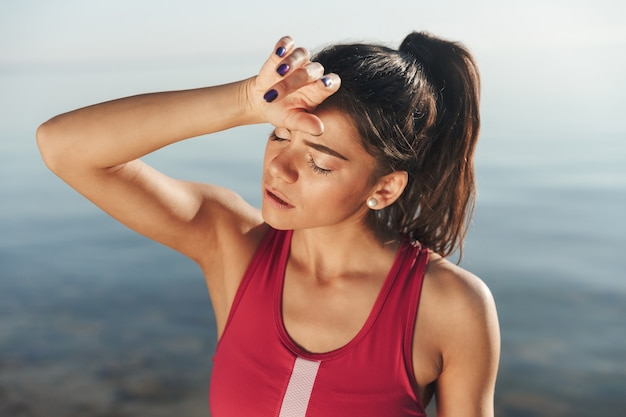 Exhausted sportswoman wiping her forehead after jogging