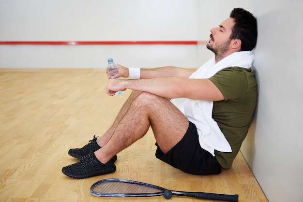 Исчерпанный игрок в сквош отдыхает на полу
