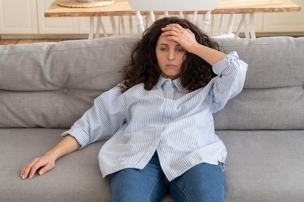 自宅のソファに横になっている疲れ果てたストレスの若い女性は圧倒されていると感じています