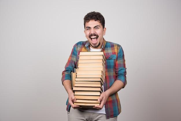 Studente esaurito con una pila di libri che urla su sfondo grigio.