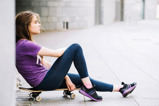 Exhausted teenager on skateboard