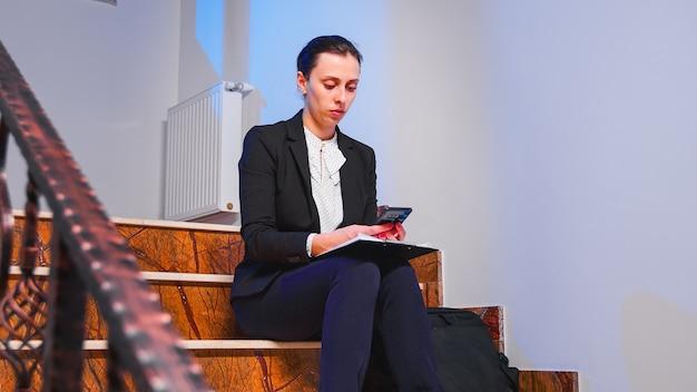 ビジネスビルの階段に座ってスマートフォンのテキストメッセージの金融プロジェクトのタスクを入力する疲れたオフィスエグゼクティブ。深夜に企業の仕事に取り組んでいる真面目な起業家