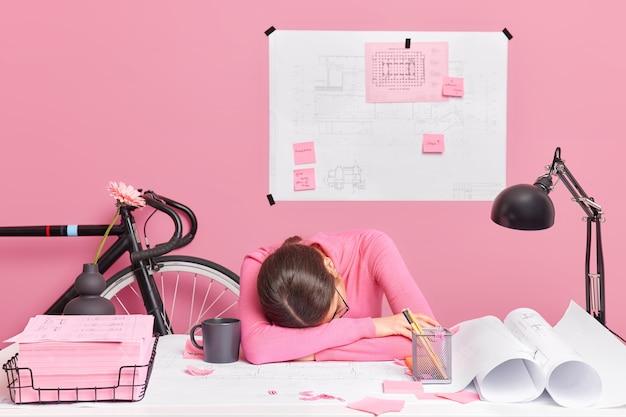 피곤하고 과로 한 여성 엔지니어가 하루 종일 새로운 디자인 프로젝트에서 작업하며 테이블에 기대어 홈 오피스에서 스케치와 청사진 포즈로 둘러싸여 잠을 자고 싶어합니다. 생산성 부족