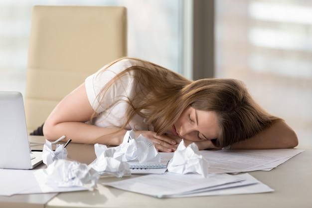 Вымотанная утомленная женщина спать на столе после переутомления в офисе