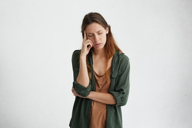 Donna esausta e stanca con i capelli scuri in piedi contro il muro bianco con gli occhi chiusi tenendo il dito indice sul tempio pensando a qualcosa. donna turbata con espressione stanca.