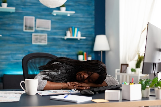 Exhausted tired workaholic black student sleeping on desk table in living room