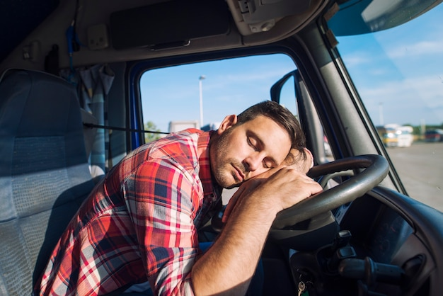 Exhausted truck driver falling asleep on steering wheel