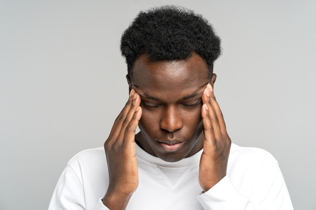 Exhausted upset african american man feeling pain suffering from migraine massaging temples studio