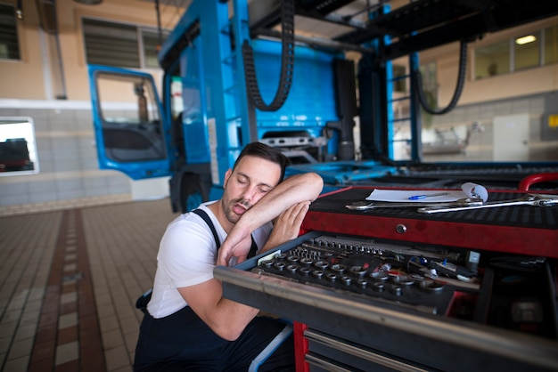 Exhausted vehicle mechanic falling asleep in his workshop