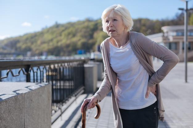 Измученная слабая аккуратная дама чувствует ужасную боль в спине во время отдыха и прогулки по городу