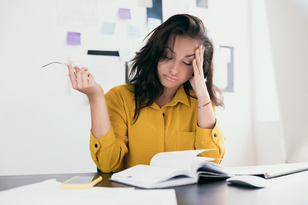 Exhausted white woman having headache at office