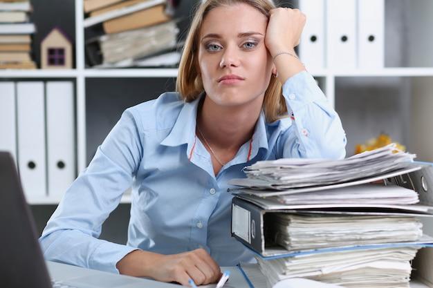 Измученная женщина в офисе с большим количеством документов