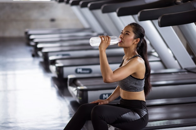 Exhausted woman drink water after run in gym