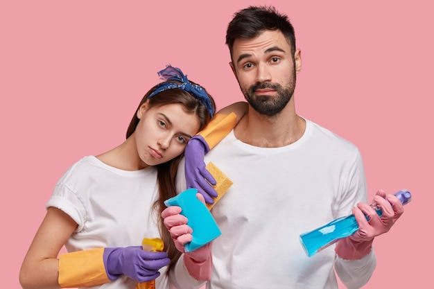 지친 여자는 남편의 어깨에 몸을 기울이고 큰 청소 후 피곤함을 느끼고 불만과 화를 느끼고 캐주얼 티셔츠를 입습니다.
