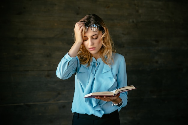 Exhausted woman looks tired, holds a book, keeps her head with hand