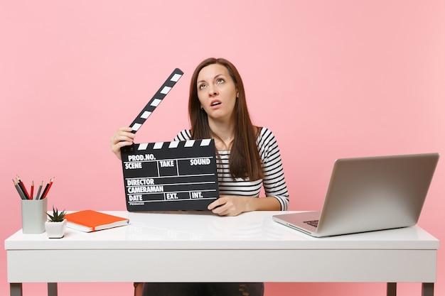 ピンクの背景に分離されたラップトップでオフィスに座っている間、古典的な黒いフィルムを持ってカチンコを作り、プロジェクトに取り組んでいる疲れた女性。業績ビジネスキャリア。スペースをコピーします。