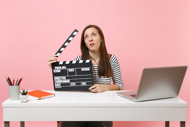 Exhausted woman rolling eyes holding classic black film making clapperboard and working on project while sit at office with laptop isolated on pink background. achievement business career. copy space.