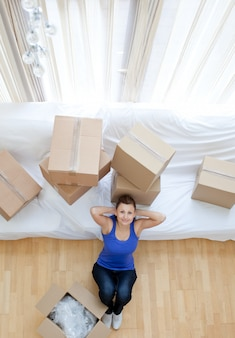 Exhausted woman sitting between boxes at home
