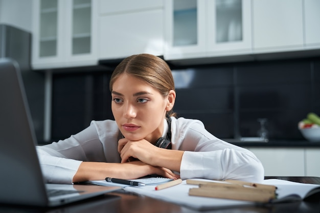 Exhausted woman sitting at table and working on laptop