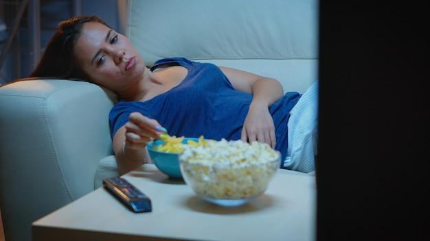 リビングルームのソファに横になっているテレビ番組を見ている疲れた女性。テレビの前で快適なソファでリラックスしたピジャマの疲れた孤独な不幸な若い女性は、夜遅くに軽食を食べるのに退屈していると感じています