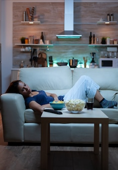 リビングルームのソファに横になっているテレビ番組を見ている疲れた女性。テレビの前で快適なソファでリラックスしたピジャマの疲れた孤独な不幸な若い女性は夜遅くに軽食を食べるのに退屈している