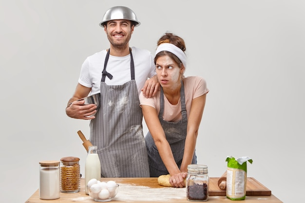 Exhausted woman with flour on face, kneads dough, tired of preparing homemade bread, cheerful man in apron leans on shoulder, holds bowl, glad to help wife on kitchen. couple make pizza together