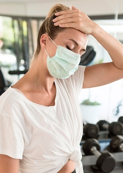 ジムで医療マスクで疲れ果てた女性