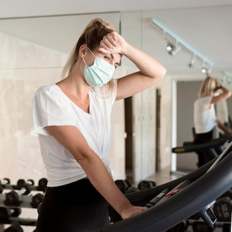Exhausted woman with medical mask at the gym