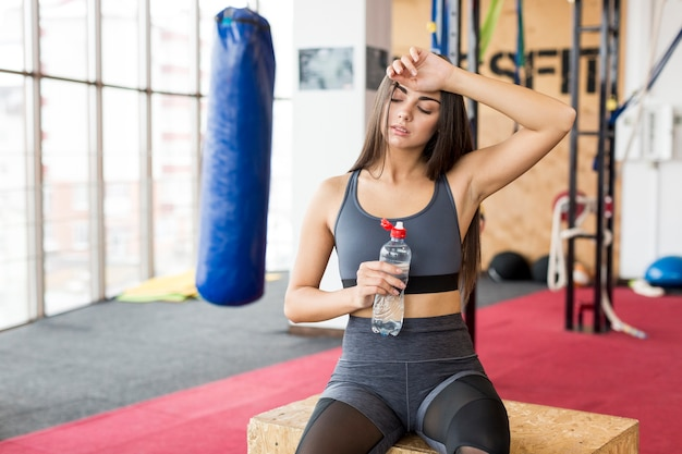 Exhausted woman with water in gym
