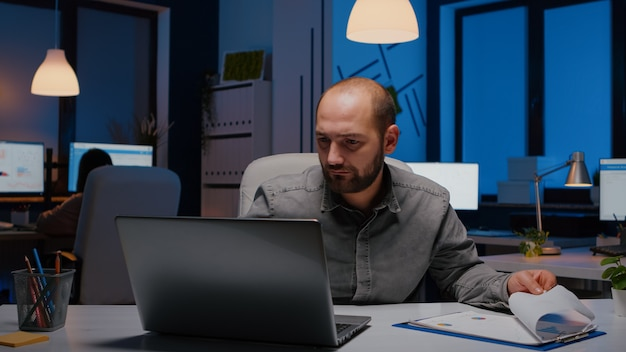 Exhausted workaholic businessman analysing marketing statistics sitting at desk table