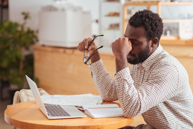 지친 노동자. 커피 하우스에 앉아 오랫동안 노트북에서 일한 코 다리를 꼬집는 피곤한 젊은 남자