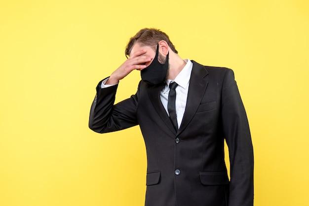 Измученный молодой человек в защитной маске стоит, положив руку на лоб