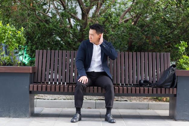 屋外の都市公園のベンチに座っている疲れ果てた若いアジア人ビジネスマンのサラリーマン。頭痛で過労男性を強調し、頭をマッサージします。うつ病の疲れた従業員が苦痛の病気の仕事に苦しんでいる