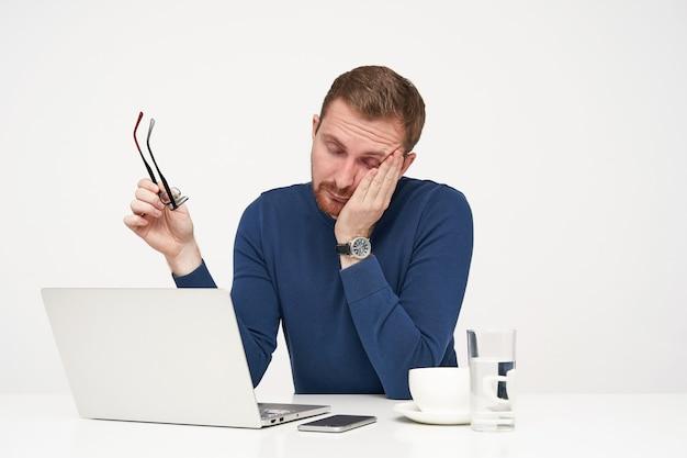 Усталый молодой бородатый светловолосый мужчина в очках держит очки в поднятой руке и закрывает глаза, сидя на белом фоне, уставший после тяжелого рабочего дня