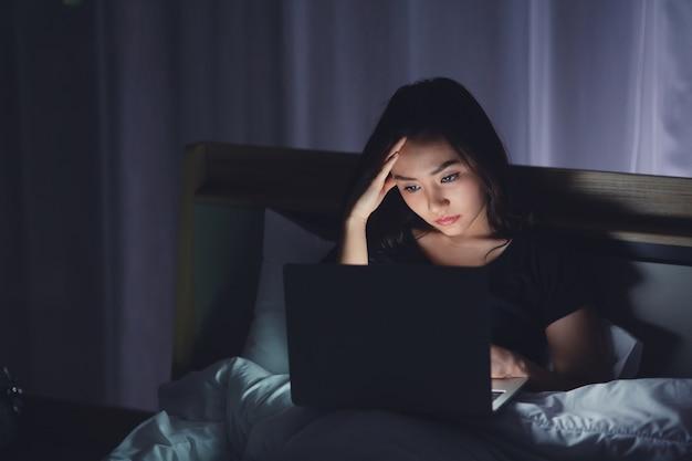 Изможденная молодая деловая женщина с помощью ноутбука работает поздно ночью на кровати