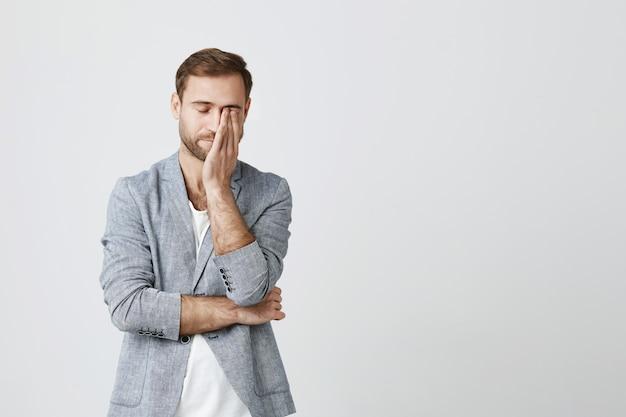 Измученный молодой бизнесмен тереть глаза, чувствуя усталость