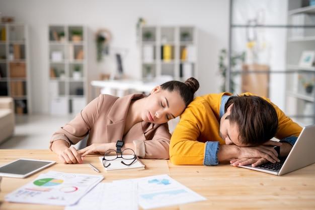 Усталые молодые коллеги, опираясь на стол с отчетными документами и ноутбуком, спят на рабочем месте