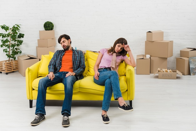 Exhausted young couple sitting on yellow sofa with moving cardboard boxes in their new home