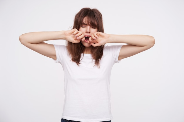 Exhausted young dark haired lady with natural makeup keeping her eyes closed while yawning with wide mouth opened, keeping hands raised while posing over white wall