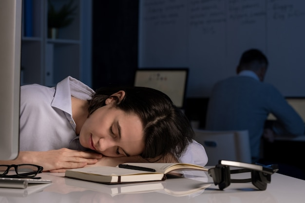 Exhausted young female hotline operator napping with her head on desk after working late in the evening with colleague