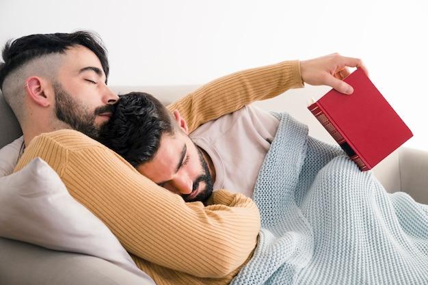 Exhausted young gay couple sleeping together on sofa