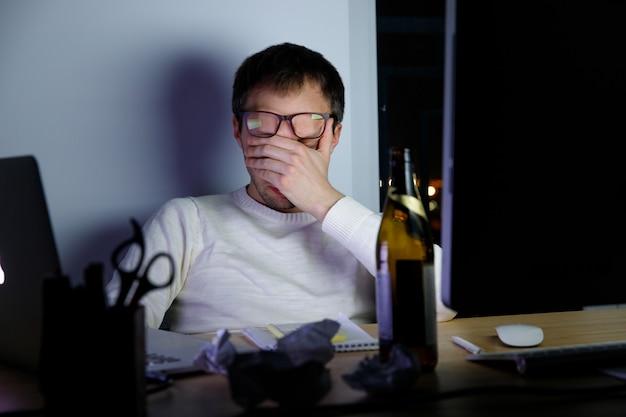 Истощенный молодой человек в очках, испытывающих напряжение во время поздней ночи на работе, пил пиво, чтобы расслабиться, засыпает от усталости.