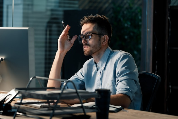 Exhausted young man in office working late