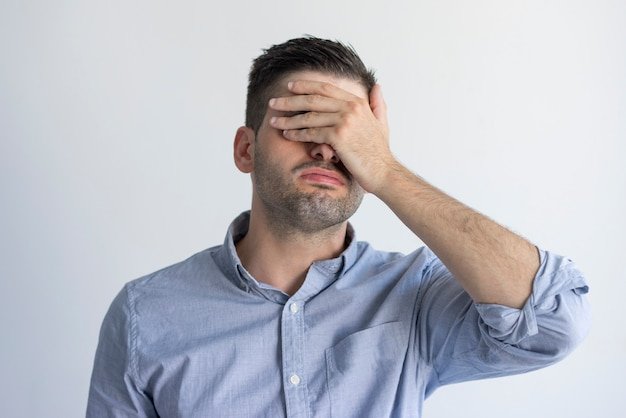 Exhausted young man with stubble covering face with hand in despair.